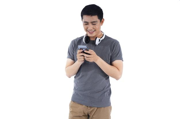 Giovane asiatico che ascolta la musica e che canta sul suo telefono