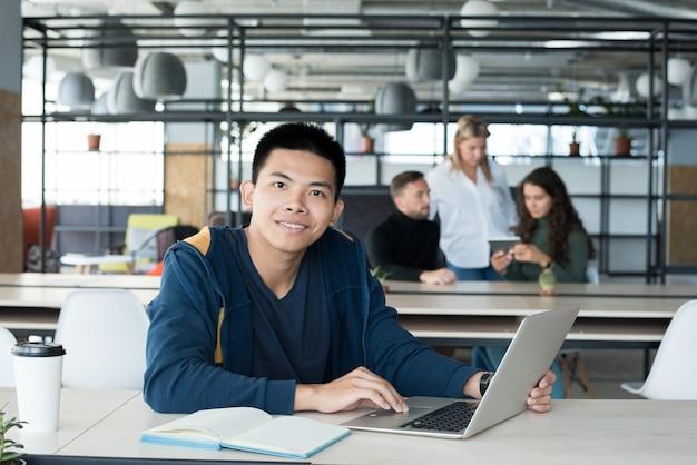 Giovane asiatico che posa nell'ufficio