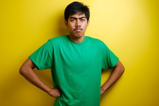 Giovane asiatico che mostra espressione facciale arrabbiata infelice cinica, guardando alla telecamera, mani sull'anca, isolato su sfondo giallo