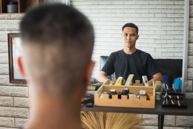 Giovane asiatico che si siede sulla sedia e guardandosi allo specchio dopo il taglio di capelli finito nel negozio di barbiere.