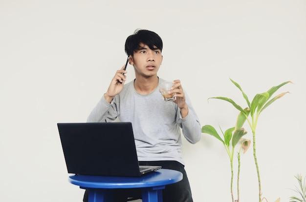 Giovane asiatico seduto davanti al laptop impegnato a fare telefonate