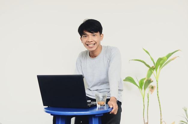 Giovane asiatico seduto al laptop con una faccia felice