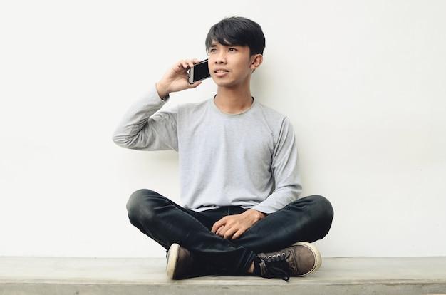 Giovane asiatico seduto a parlare al telefono