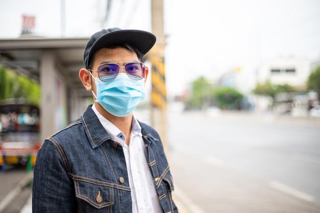 Giovane asiatico che sta nella città e che indossa la maschera di protezione sul fronte per protezione