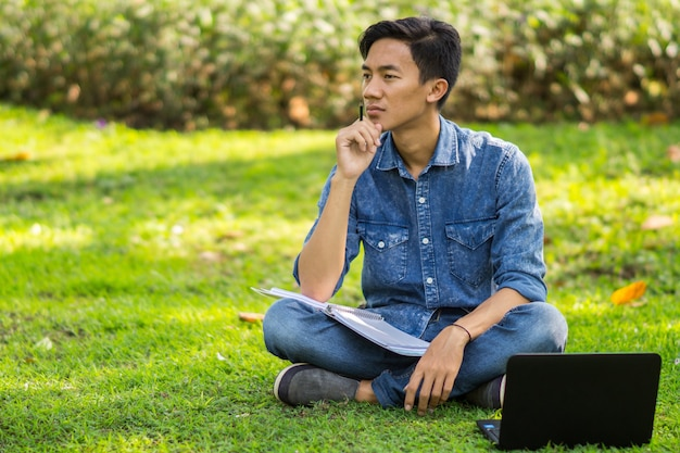 Giovane asiatico che pensa alle idee al parco utilizzando il computer portatile