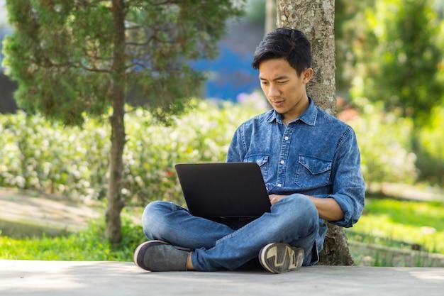 Giovane asiatico che per mezzo del computer all'aperto