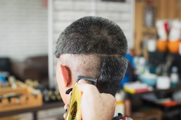 Giovane asiatico che ha i capelli grigi essendo taglio di capelli con tagliatore elettrico dal barbiere professionista nel negozio di barbiere.