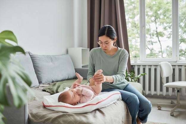 Giovane madre asiatica seduta sul divano e preoccupata per il suo bambino mentre è sdraiata sul letto nella stanza