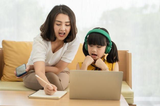 Giovane madre asiatica con il computer portatile che insegna al bambino a homeme