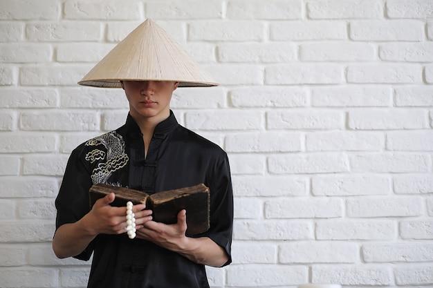 Giovane novizio asiatico su uno sfondo di muro di mattoni bianchi