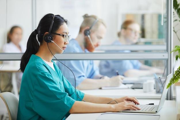 Giovane operatore asiatico in uniforme e cuffia avricolare che si siede al tavolo e che scrive sul computer portatile all'ospedale