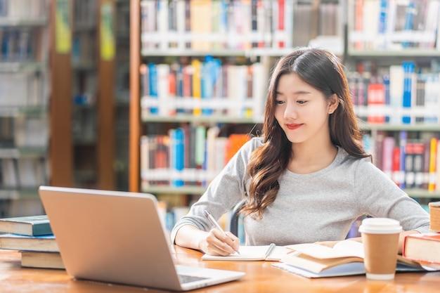 Giovane studente asiatico in abito casual che fa i compiti e usa il computer portatile tecnologico in biblioteca
