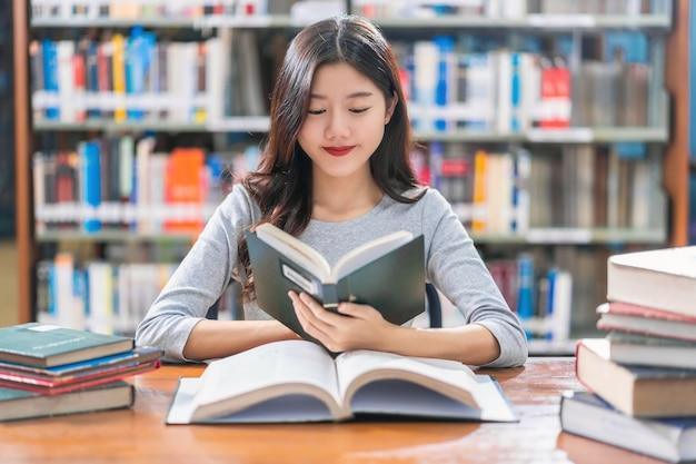 Giovane studente asiatico in abito casual che legge il libro sul tavolo di legno nella biblioteca dell'università