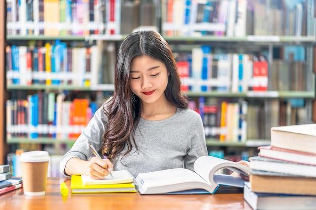 Giovane studente asiatico in vestito casuale che legge e che fa i compiti in biblioteca dell'università