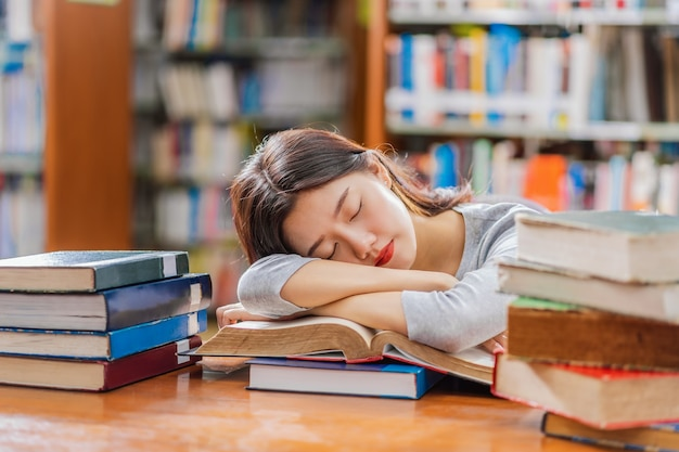 Giovane studente asiatico in abito casual che legge e dorme sul tavolo di legno con vari libri i