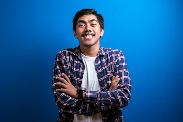Giovani studenti asiatici sorrisero alla telecamera con aria fiduciosa mentre mettevano entrambe le mani sul petto su sfondo blu. scatti in studio