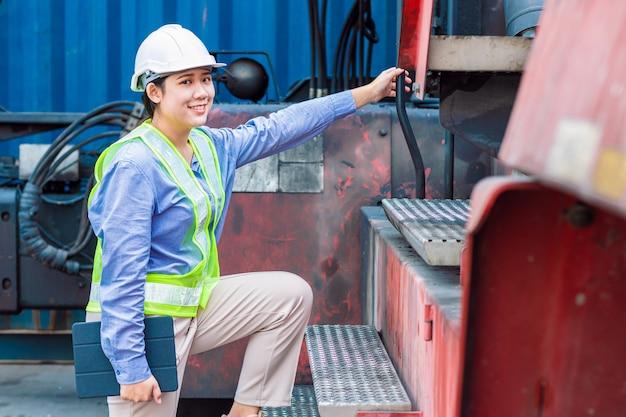 Asian giovane adolescente felice sorriso ingegnere lavoratore che lavora con la macchina dell'industria pesante con tuta di sicurezza e elmetto protettivo, guardando la telecamera.