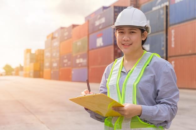 Il giovane operaio felice teenager asiatico che controlla le azione nel lavoro del porto di spedizione gestisce i contenitori di carico dell'esportazione dell'importazione.