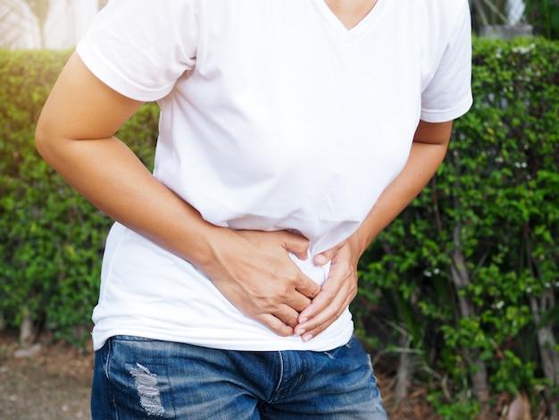 Giovani donne tailandesi asiatiche che soffrono di mal di stomaco grave, mal di stomaco o dolore mestruale.