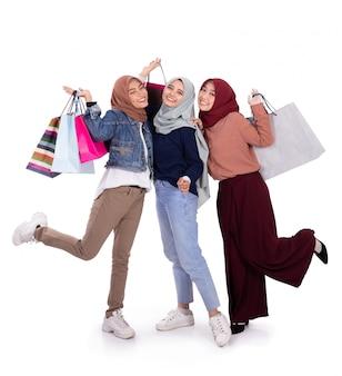 Giovani donne velate asiatiche che trasportano un certo sacco di carta dopo la compera