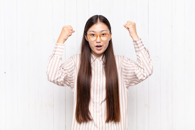 Giovane donna asiatica che celebra un incredibile successo come una vincitrice, che sembra eccitata e felice di dire prendi!