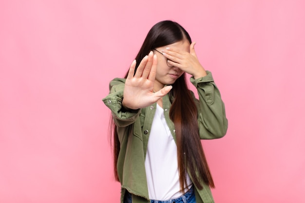 Giovane donna asiatica che copre il viso con la mano e mette l'altra mano davanti per fermare la fotocamera, rifiutando foto o immagini