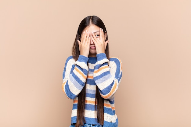 Giovane donna asiatica che copre il viso con le mani, sbirciando tra le dita isolate