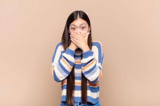Giovane donna asiatica che copre la bocca con le mani con un'espressione scioccata e sorpresa, mantenendo un segreto o dicendo oops