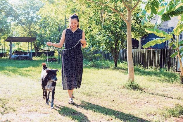 Cane asiatico della giovane donna che cammina nel giardino del cortile a casa la mattina