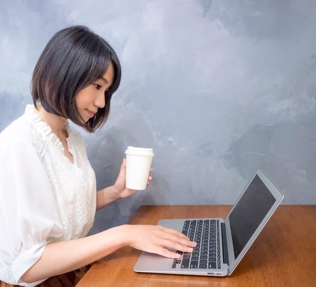 La giovane donna asiatica beve davanti al computer portatile