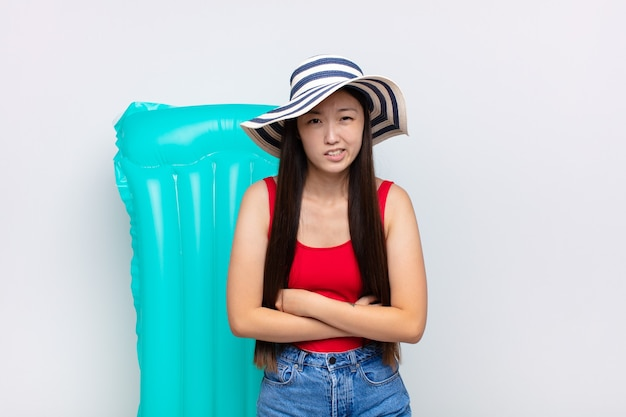 Giovane donna asiatica che si sente ansiosa, malata, malata e infelice, che soffre di un doloroso mal di stomaco o influenza. concetto di estate