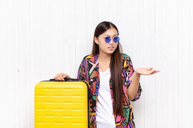Giovane donna asiatica che si sente incapace e confusa, incerta su quale scelta o opzione scegliere, chiedendosi. concetto di vacanze