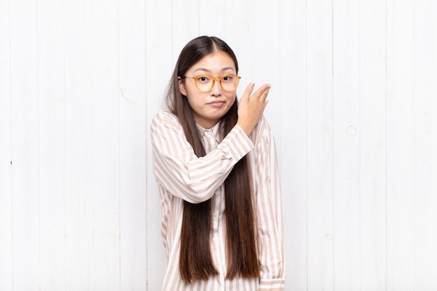 Giovane donna asiatica che si sente confusa e incapace, chiedendosi una spiegazione o un pensiero dubbioso
