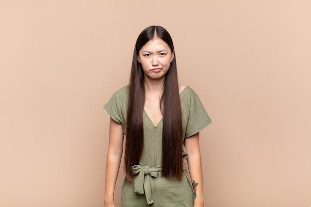 Giovane donna asiatica che si sente confusa e dubbiosa, chiedendosi o cercando di scegliere o prendere una decisione