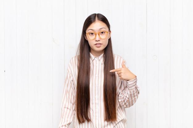 Giovane donna asiatica che si sente confusa, perplessa e insicura, indicando se stessa chiedendosi e chiedendo chi, io?