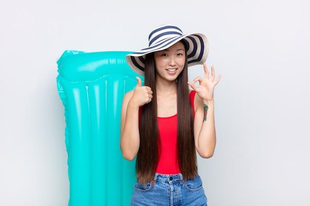 Giovane donna asiatica che si sente felice, stupita, soddisfatta e sorpresa, mostrando i gesti ok e il pollice in alto, sorridente concetto di estate