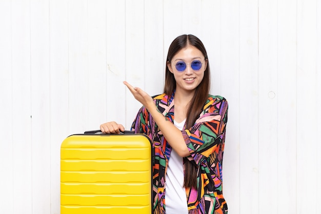 Giovane donna asiatica che si sente felice e allegra, sorridente isolata