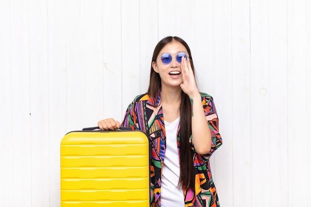Giovane donna asiatica che si sente felice, eccitata e positiva, dando un grande grido con le mani vicino alla bocca, chiamando