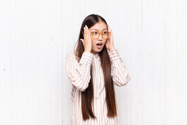 Giovane donna asiatica che si sente felice, eccitata e sorpresa, guardando di lato con entrambe le mani sul viso