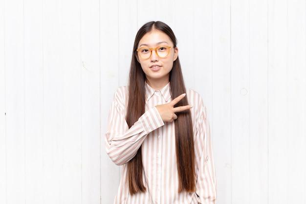 Giovane donna asiatica che si sente felice, positiva e di successo, con la mano che fa la forma a v sul petto, mostrando vittoria o pace