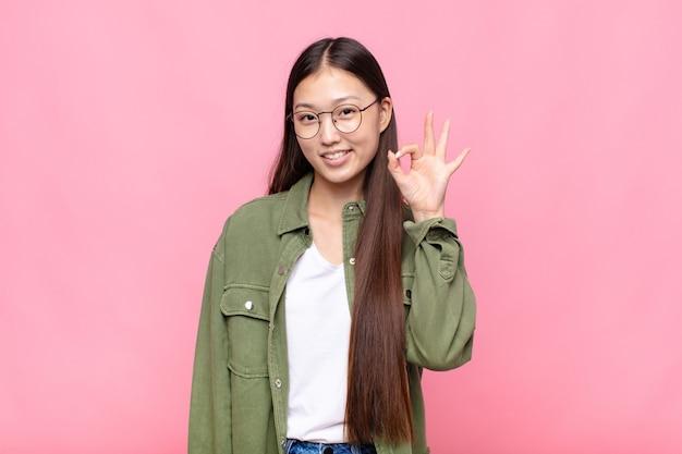 Giovane donna asiatica che si sente felice, rilassata e soddisfatta, mostrando l'approvazione con il gesto giusto, sorridendo
