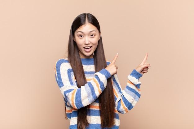 Giovane donna asiatica che si sente gioiosa e sorpresa, sorridendo con un'espressione scioccata e indicando il lato