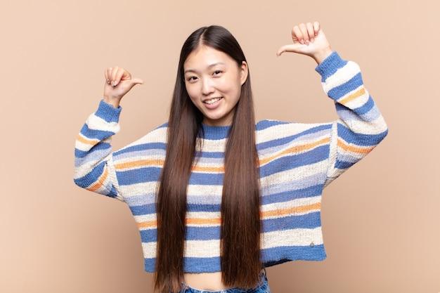 Giovane donna asiatica che si sente orgogliosa, arrogante e sicura di sé, che sembra soddisfatta e di successo, indicando se stessa