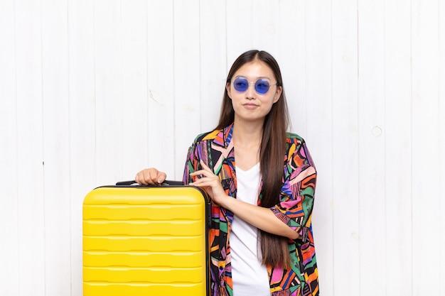 Giovane donna asiatica che si sente orgogliosa, maliziosa e arrogante mentre trama un piano malvagio o pensa a un trucco. concetto di vacanze