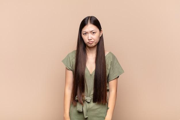 Giovane donna asiatica che si sente triste e piagnucolona con uno sguardo infelice, piange con un atteggiamento negativo e frustrato