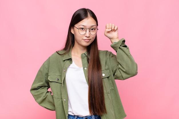 Giovane donna asiatica che si sente seria, forte e ribelle, alza il pugno, protesta o combatte per la rivoluzione