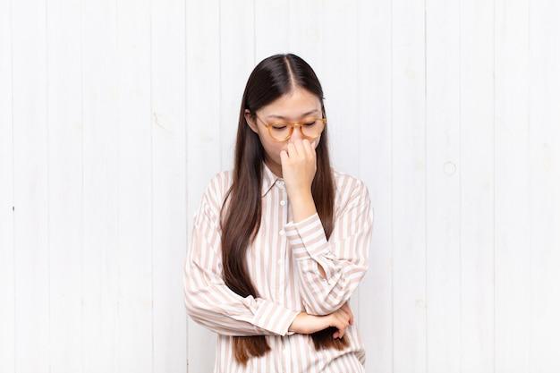 Giovane donna asiatica che si sente seria, premurosa e preoccupata, fissando lateralmente con la mano premuta contro il mento