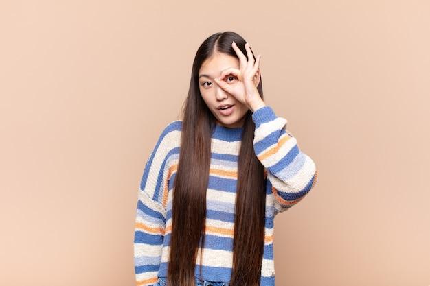 Giovane donna asiatica che si sente scioccata, stupita e sorpresa, tenendo in mano gli occhiali con uno sguardo stupito e incredulo