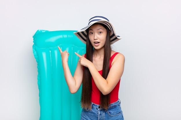 Giovane donna asiatica che si sente scioccata e sorpresa, indicando lo spazio di copia sul lato con uno sguardo stupito e a bocca aperta. concetto di estate