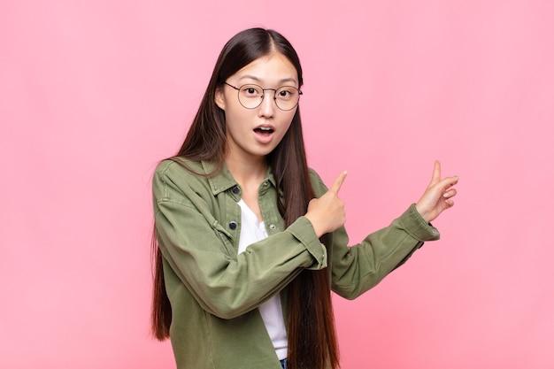 Giovane donna asiatica che si sente scioccata e sorpresa, indicando lo spazio di copia sul lato con uno sguardo stupito e a bocca aperta